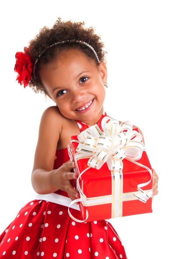 La muchacha sonriente con el pelo de los rizos da una caja de regalo en manos imagenes de archivo