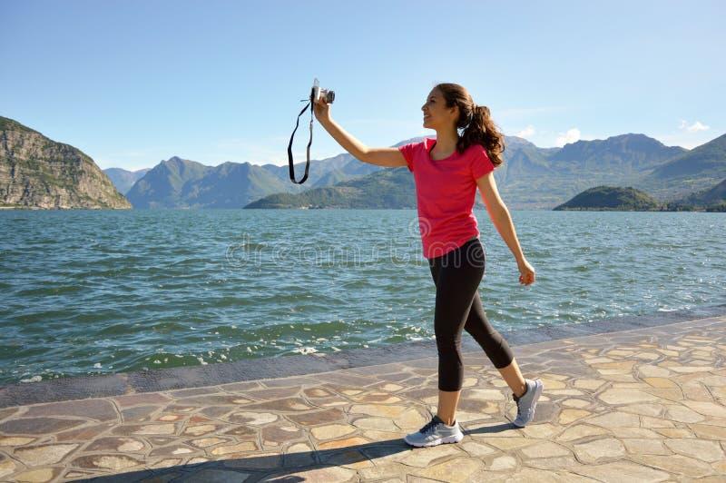 La muchacha sonriente de la aptitud toma el selfie con la cámara mirrorless con paisaje hermoso del lago en el fondo fotografía de archivo libre de regalías