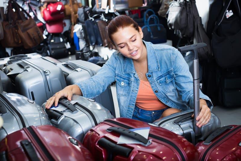 La muchacha sonriente del adolescente que elige el nuevo equipaje plástico grande empaqueta fotografía de archivo