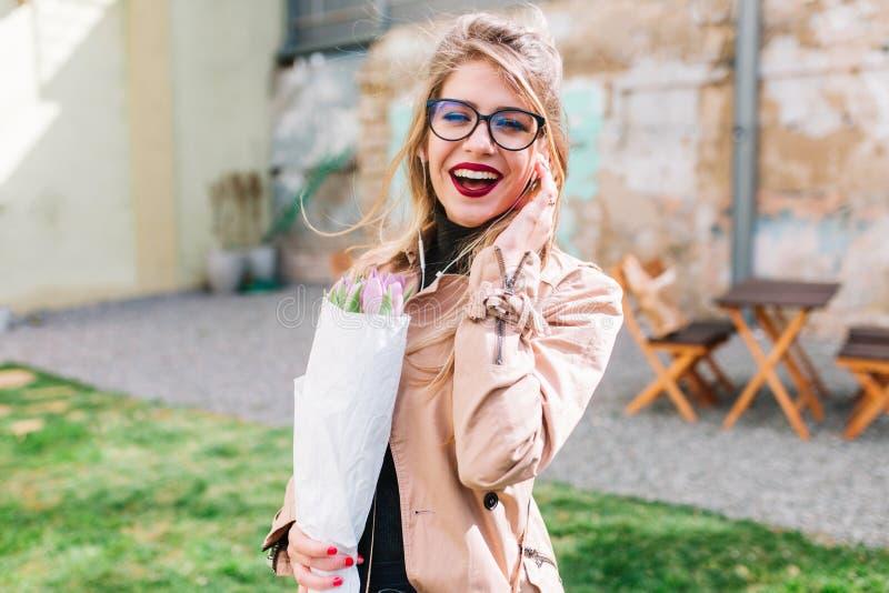 La muchacha sonriente eficaz en vidrios compró el ramo del tulipán en la floristería para el cumpleaños de su mejor amigo Se?ora  foto de archivo libre de regalías