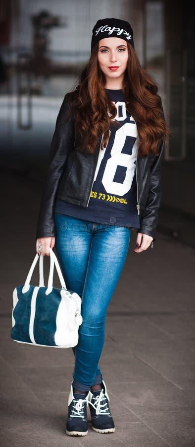 La muchacha sonriente elegante con un bolso grande imagenes de archivo