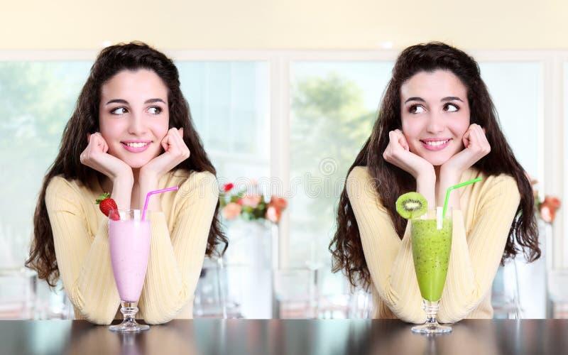 La muchacha sonriente en café bebe la fresa y el kiwi del batido de leche imagen de archivo