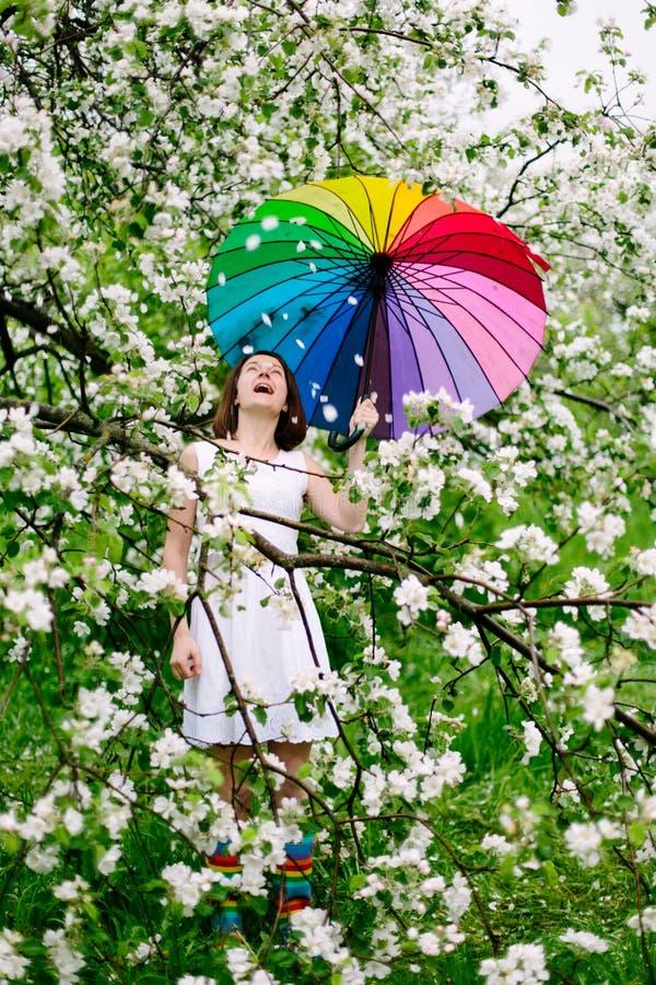 La muchacha sonriente en el vestido blanco y las arco iris-botas que se colocan en la floración cultivan un huerto con el arco ir imagen de archivo libre de regalías