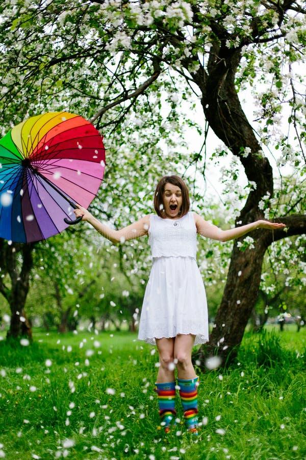 La muchacha sonriente en el vestido blanco y las arco iris-botas que se colocan en la floración cultivan un huerto con el arco ir fotografía de archivo libre de regalías