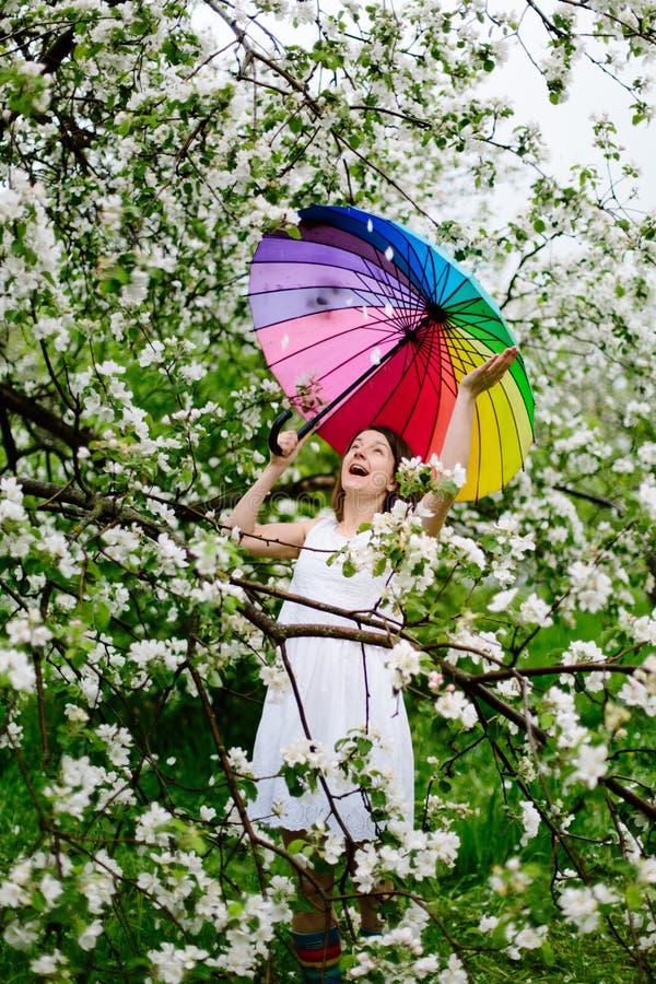 La muchacha sonriente en el vestido blanco y las arco iris-botas que se colocan en la floración cultivan un huerto con el arco ir foto de archivo libre de regalías