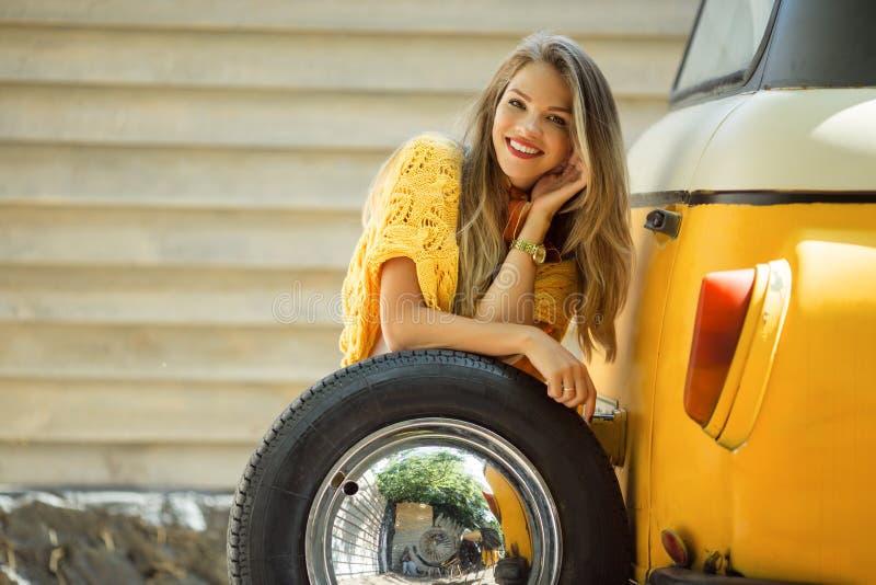 La muchacha sonriente feliz está llevando el suéter amarillo está presentando con la rueda auto cerca del autobús retro viejo, co imagen de archivo