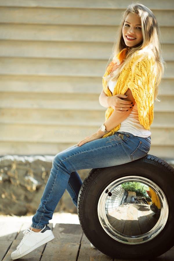La muchacha sonriente feliz está llevando el suéter amarillo se está sentando en el neumático cerca del autobús retro viejo, conc fotos de archivo