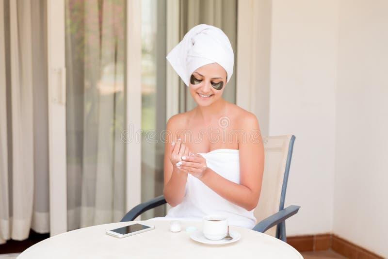 La muchacha sonriente feliz mancha las manos con crema de piel hidratante Crema corporal de aplicaci?n femenina joven Skincare y  foto de archivo libre de regalías