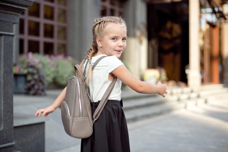 La muchacha sonriente feliz va a ense?ar por primera vez con el bolso va a la escuela primaria El alumno va estudio con la mochil fotos de archivo