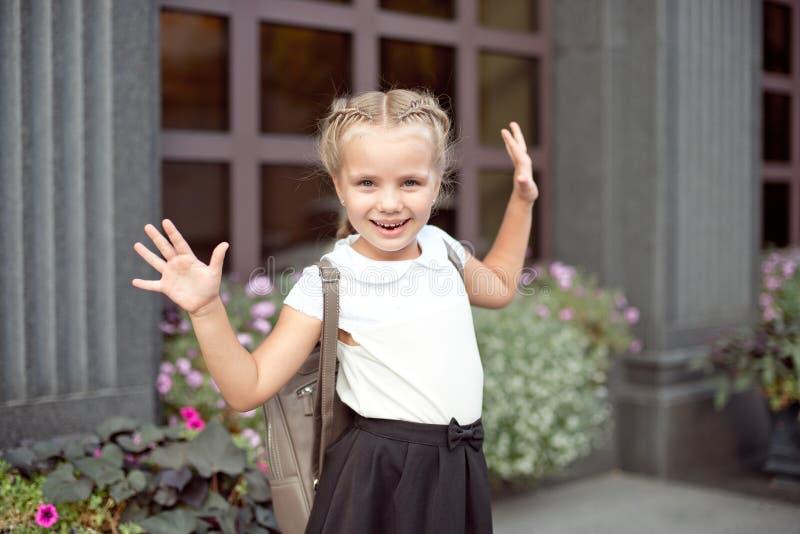 La muchacha sonriente feliz va a ense?ar por primera vez con el bolso va a la escuela primaria fotografía de archivo
