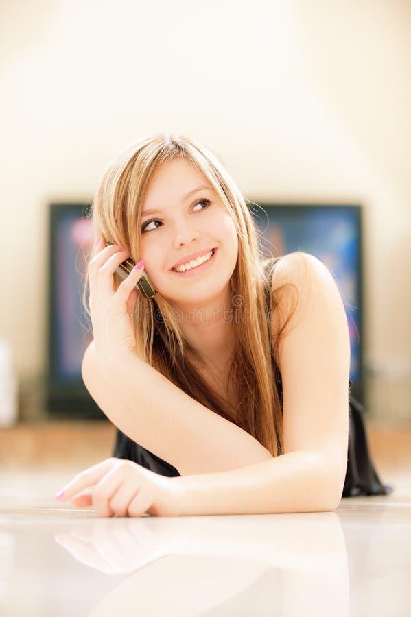 La muchacha sonriente habla por el teléfono foto de archivo