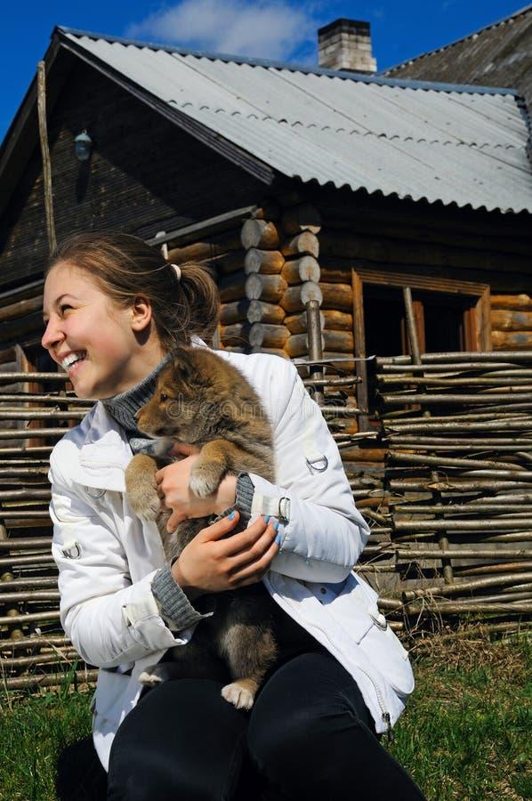 La muchacha sonriente hermosa acaricia un perrito fotos de archivo
