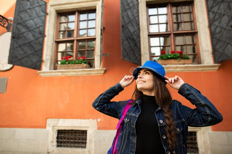 La muchacha sonriente hermosa en un sombrero azul presenta cerca de la casa roja vieja fotos de archivo libres de regalías