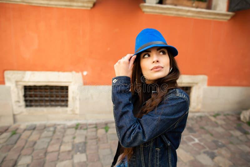 La muchacha sonriente hermosa en un sombrero azul presenta cerca de la casa roja vieja imagenes de archivo