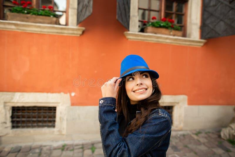 La muchacha sonriente hermosa en un sombrero azul presenta cerca de la casa roja vieja foto de archivo