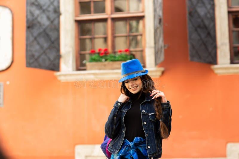 La muchacha sonriente hermosa en un sombrero azul presenta cerca de la casa roja vieja imágenes de archivo libres de regalías