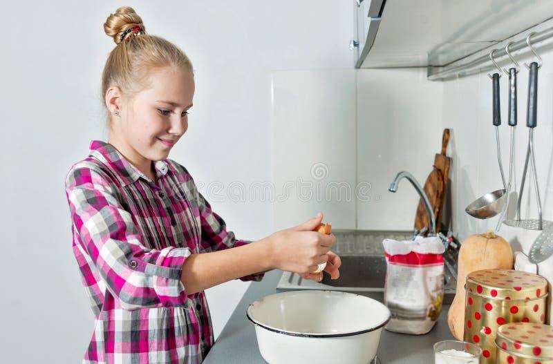 La muchacha sonriente hermosa joven rompe un huevo en plato profundo El cocinar rubio lindo en una cocina casera fotos de archivo libres de regalías