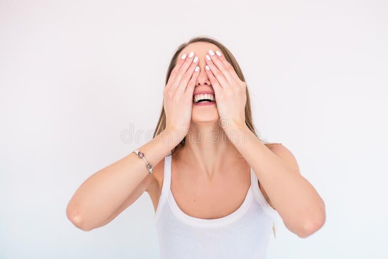 La muchacha sonriente joven en la camiseta blanca la cierra los ojos con sus manos fotos de archivo