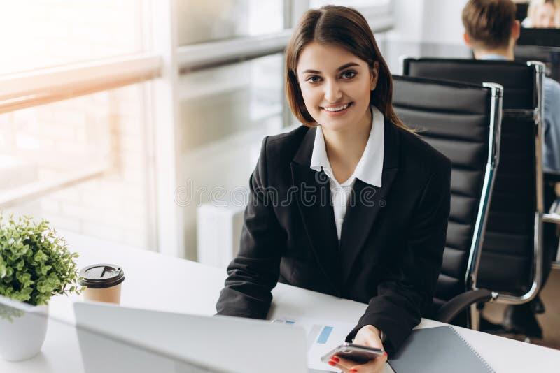 La muchacha sonriente joven y acertada hermosa se sienta en la tabla en su oficina Empresaria imágenes de archivo libres de regalías