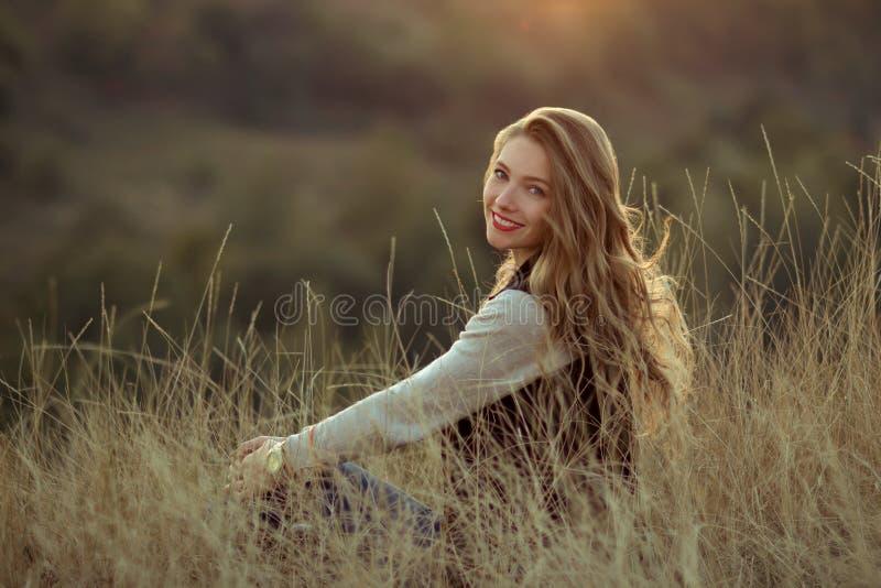 La muchacha sonriente linda con sonrisa maravillosa, linda, blanca y los labios rojos mira puesta del sol, se sienta en las colin fotografía de archivo
