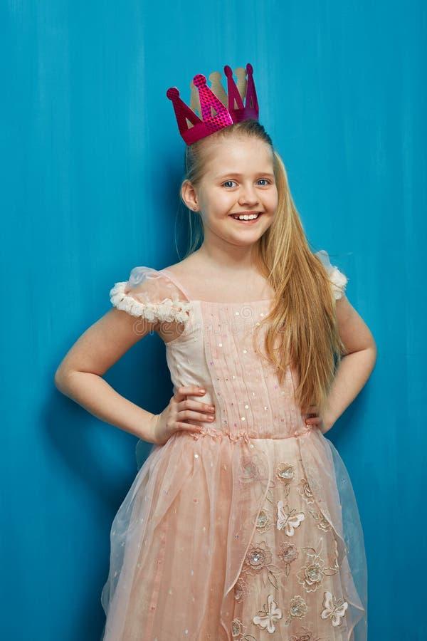 La muchacha sonriente que lleva el vestido rosado elegante y el papel coronan foto de archivo libre de regalías