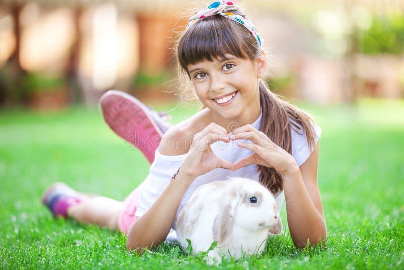 La muchacha sonriente que muestra un corazón firma con sus manos sobre un conejo del animal doméstico imagen de archivo