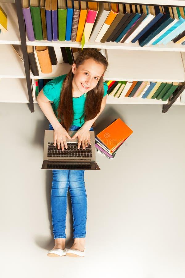 La muchacha sonriente que se sienta en piso con el ordenador portátil mira para arriba imágenes de archivo libres de regalías