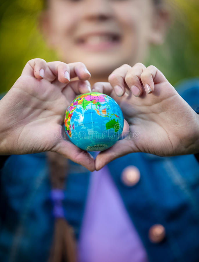 La muchacha sonriente que sostenía el globo en manos dobló en la forma del corazón imagen de archivo