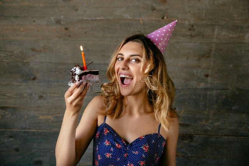 La muchacha sonriente quiere comer un pedazo de torta de cumpleaños fotos de archivo libres de regalías