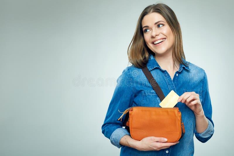 La muchacha sonriente saca la tarjeta de crédito del oro del bolso imagenes de archivo
