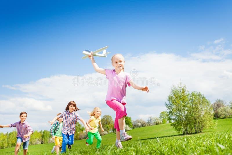 La muchacha sonriente sostiene el juguete del aeroplano con el funcionamiento de los niños foto de archivo libre de regalías