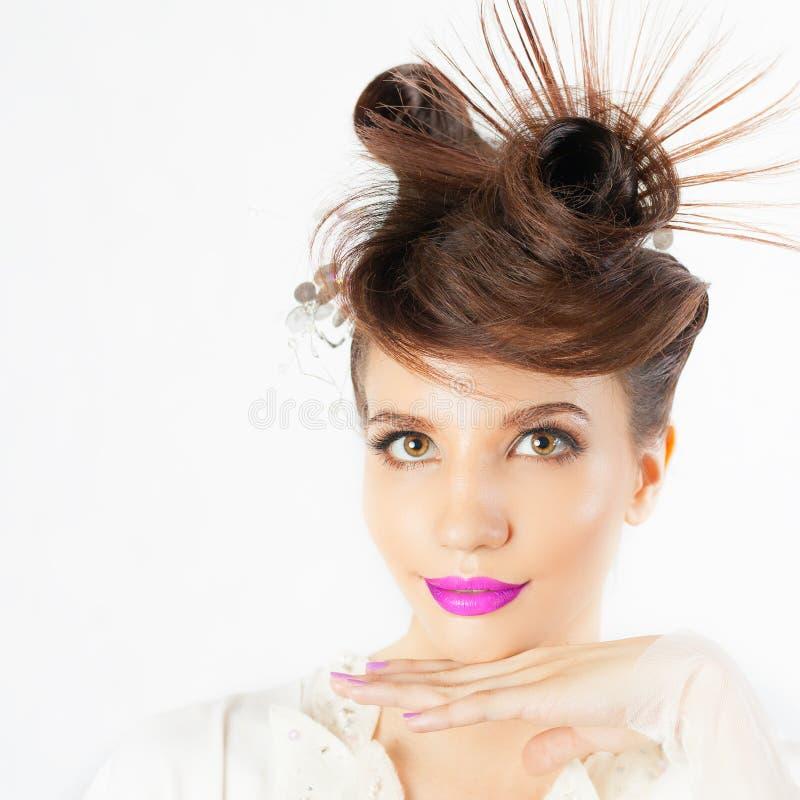 La muchacha sorprendida con el peinado de lujo en el blanco empañó el fondo imagen de archivo libre de regalías