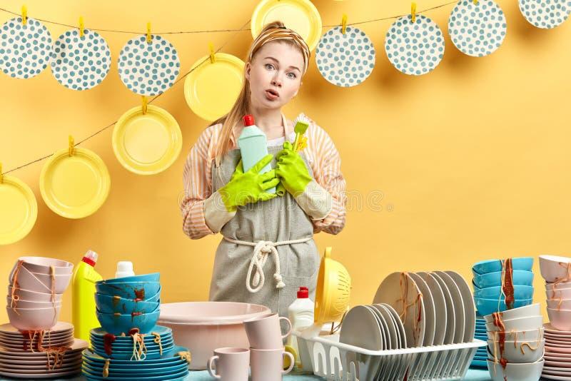 La muchacha sorprendida descontentada vacilante sostiene el cepillo y el líquido de la limpieza imagenes de archivo