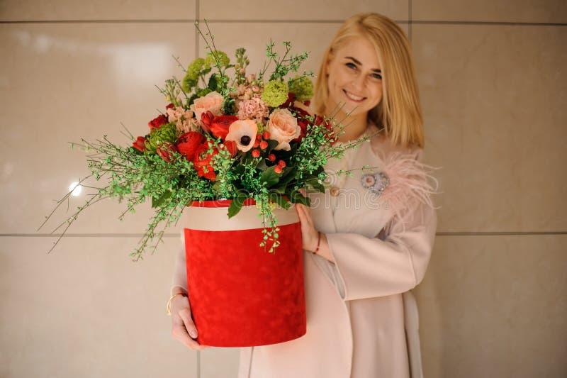 La muchacha sostiene la caja roja del sombrero con las flores imágenes de archivo libres de regalías