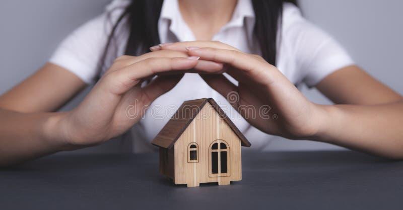 La muchacha sostiene la casa fotos de archivo