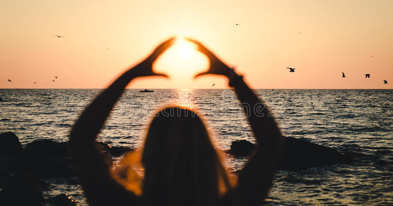 La muchacha sostiene el sol cerca del mar en la puesta del sol foto de archivo