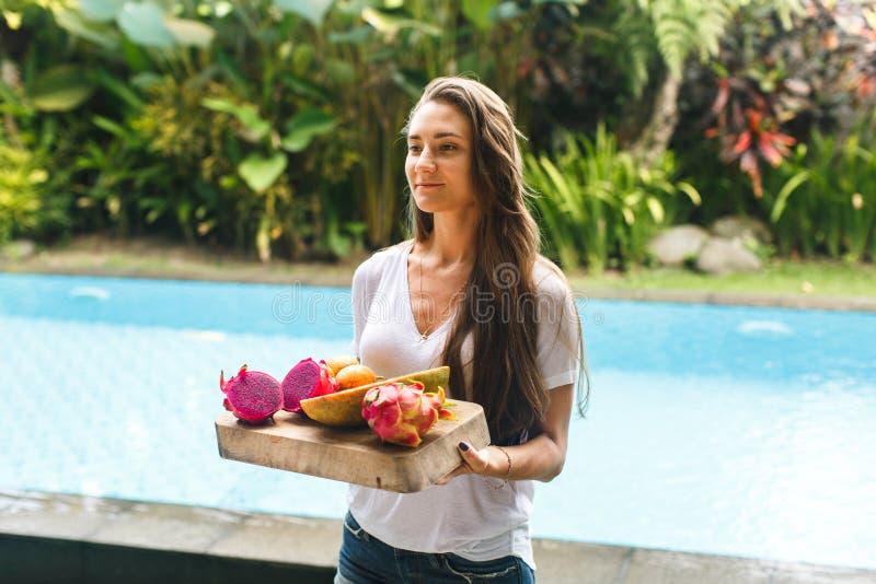 La muchacha sostiene la bandeja de frutas exóticas en chalet fotos de archivo libres de regalías