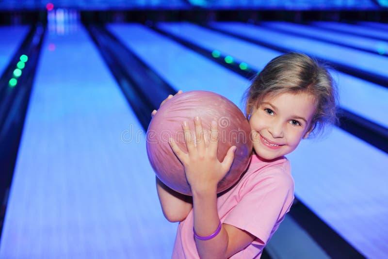 La muchacha sostiene la bola en club del bowlinng imagen de archivo libre de regalías