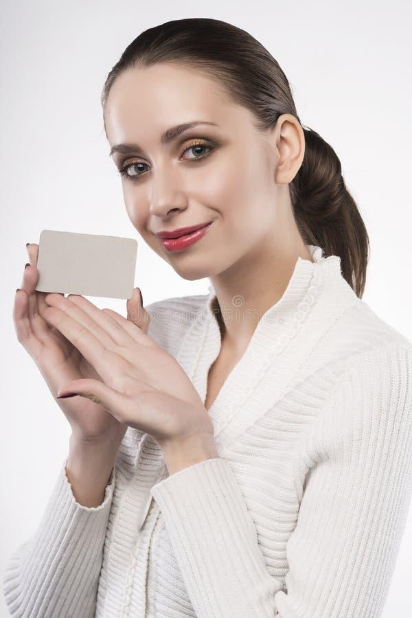 La muchacha sostiene la tarjeta clara aislada en blanco foto de archivo libre de regalías