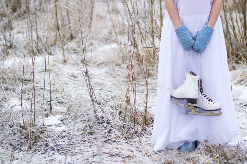 La muchacha sostiene los patines para patinaje artístico fotografía de archivo