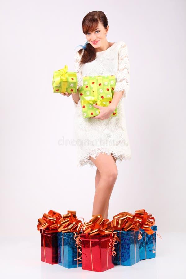 La muchacha sostiene los rectángulos con los regalos, se coloca entre los rectángulos de regalo imágenes de archivo libres de regalías