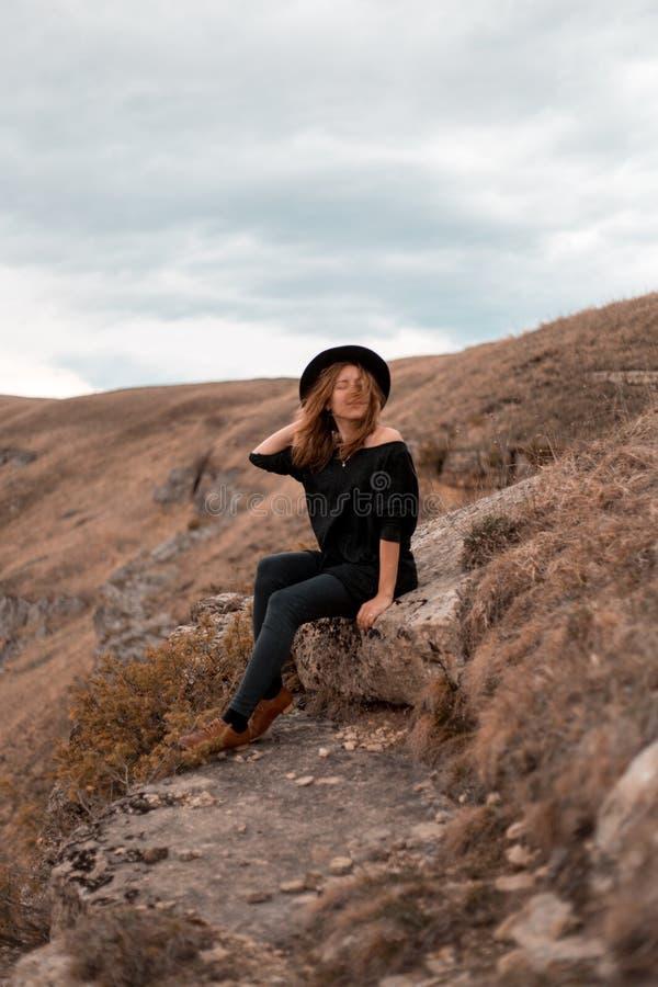 La muchacha sostiene sombrero, d?ndole vuelta de nuevo al valle con las monta?as siéntese en roca fotografía de archivo