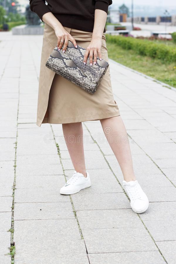 La muchacha sostiene un bolso de cuero de moda en su mano y paseos abajo de la calle, concepto de un equipo del verano fotografía de archivo