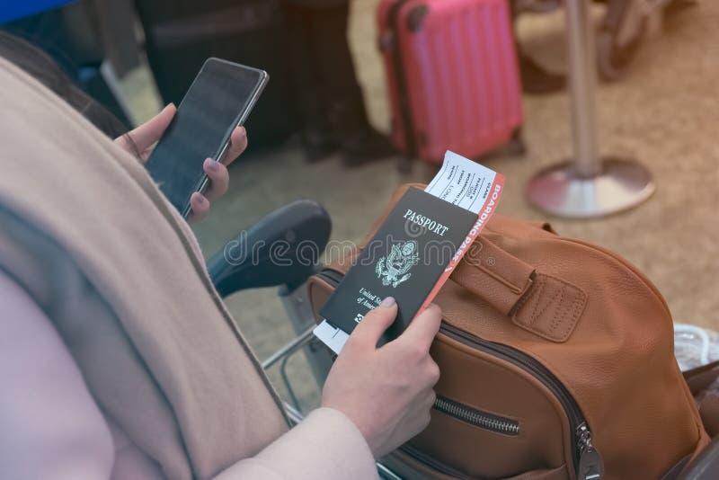 La muchacha sostiene un móvil y un pasaporte con un documento de embarque en ella fotos de archivo