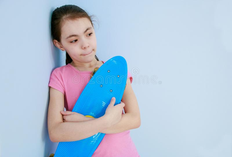 La muchacha sostiene un patín azul que se coloca en la pared que piensa en algo fotos de archivo libres de regalías