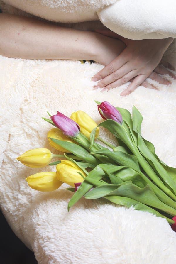 La muchacha sostiene un ramo de tulipanes amarillos y rosados Mienten en un juguete suave grande, que es abrazado por una mujer fotos de archivo
