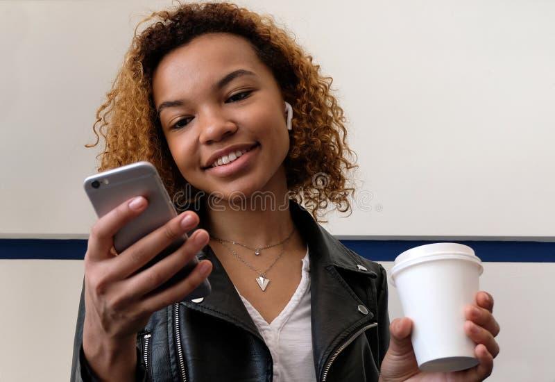 La muchacha sostiene un vidrio blanco en su mano, mira en el teléfono y sonríe Una mujer negra moderna joven hermosa, en un enchu imagenes de archivo
