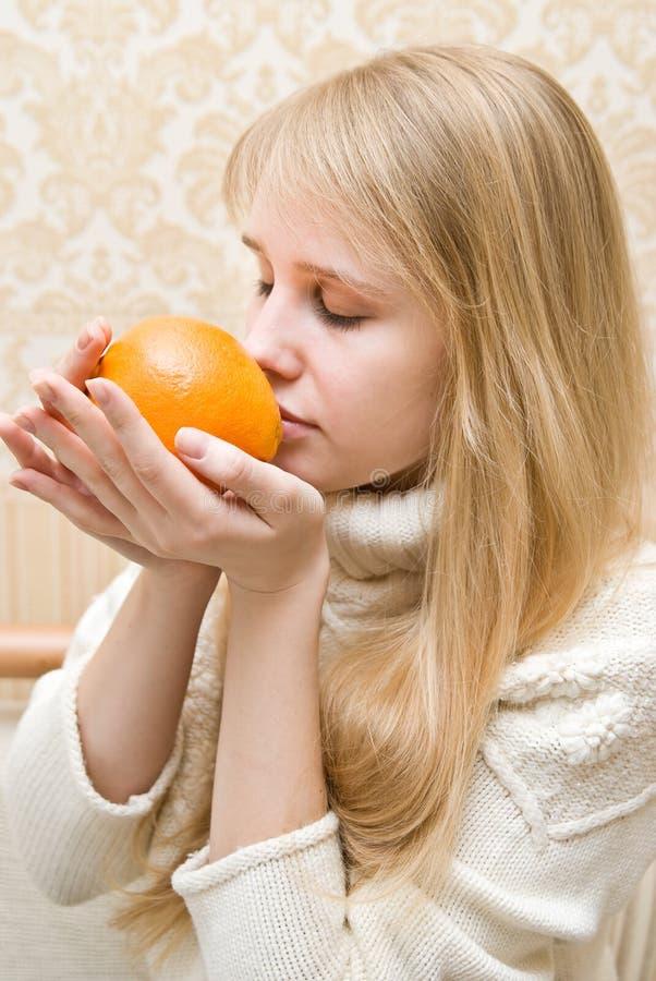 La muchacha sostiene una naranja imagenes de archivo