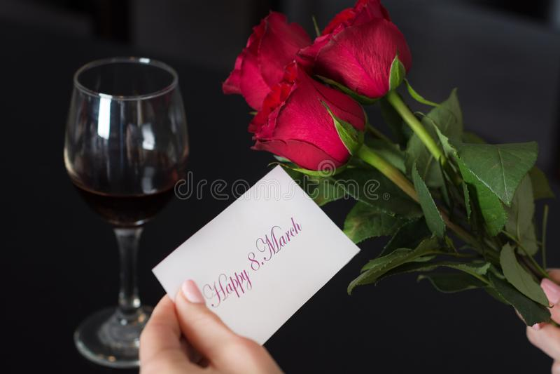 La muchacha sostiene una tarjeta de papel con un mensaje 8 felices Marzo en su mano y rosa y copa de vino rojas en la tabla negra fotos de archivo libres de regalías