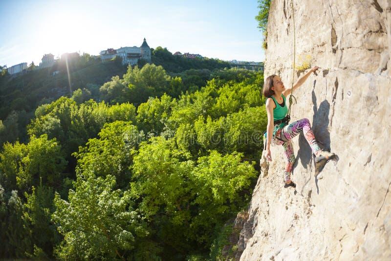 La muchacha sube la roca foto de archivo libre de regalías